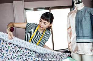 Japanese female fashion designer working in her studio,  holding roll of fabric.の写真素材 [FYI02265645]
