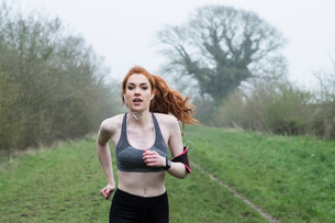 Young woman with long red hair wearing sports kit, exercising outdoors, looking at camera.の写真素材 [FYI02265653]
