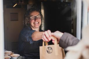 Smiling woman wearing glasses handing  brown paper shopping bag through window of bakery.の写真素材 [FYI02265664]