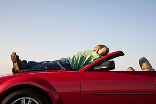 A senior male relaxing on the hood of his convertible sport car.の写真素材 [FYI02265671]