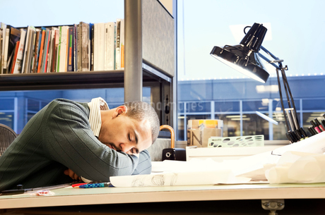 A Black man architect/designer taking a nap in his corporate office.の写真素材 [FYI02265686]