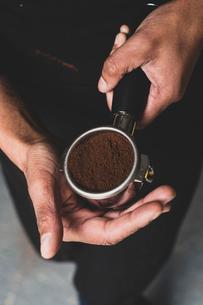 High angle close up of person holding espresso machine portafilter with ground espresso.の写真素材 [FYI02265692]