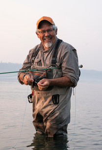 Caucasian senior male tying a fly on his fly fishing line while fishing for salmon and searun cutthrの写真素材 [FYI02265699]