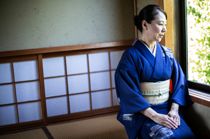 Japanese woman wearing traditional bright blue kimono with cream coloured obi kneeling on floor in tの写真素材 [FYI02265701]