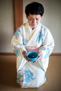 Japanese woman wearing traditional white kimono with blue floral pattern kneeling on floor during teの写真素材 [FYI02265702]