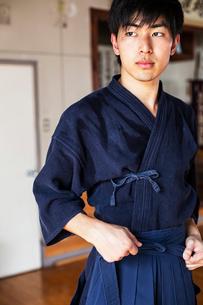 Male Japanese Kendo fighter tying belt of his blue Kendo uniform.の写真素材 [FYI02265712]