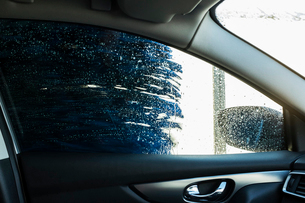 View from the inside of a car in an automated car wash, blue washers and soapy water over the windowの写真素材 [FYI02265714]