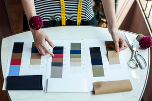 High angle close up of fashion designer working in her studio, looking at fabric samples.の写真素材 [FYI02265721]