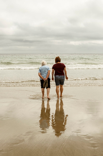 Rear view of a grey haired elderly woman and a younger woman paddling with shoes off in shallow waveの写真素材 [FYI02265722]
