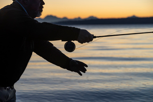 A silhouette of a fly fisherman casting at sunrise for searun coastal cutthroat trout on a beach onの写真素材 [FYI02265732]