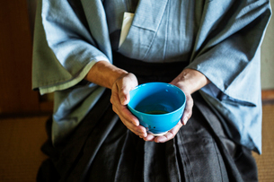 High angle close up of Japanese man wearing traditional kimono kneeling on floor holding blue tea boの写真素材 [FYI02265755]