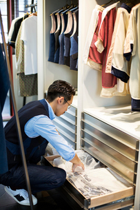 Japanese salesman with moustache wearing glasses kneeling in front of open drawer in clothing store.の写真素材 [FYI02265761]