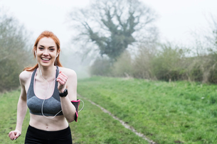 Smiling young woman with long red hair wearing sports kit, exercising outdoors, looking at camera.の写真素材 [FYI02265773]