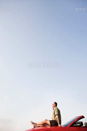 Caucasian male relaxing on the hood of his convertible sports car.の写真素材 [FYI02265789]