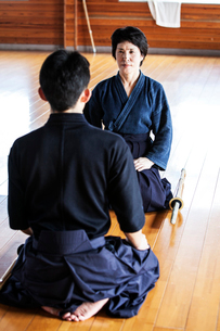 Female and male Japanese Kendo fighters kneeling opposite each other on wooden floor.の写真素材 [FYI02265800]