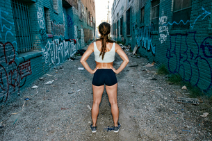Rear view of female athlete standing on street lined with buildings covered in graffiti.の写真素材 [FYI02265803]