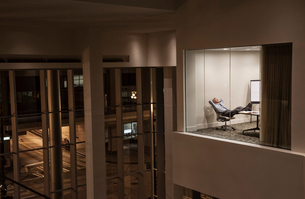 A view looking into a conference room at night  with a single businessman at a conference table.の写真素材 [FYI02265815]