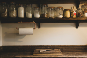 Wooden chopping board and knife on vintage wooden kitchen cupboard, row of glass jars with cooking iの写真素材 [FYI02265817]