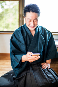 Japanese man wearing kimono sitting on floor in traditional Japanese house, using mobile phone.の写真素材 [FYI02265819]