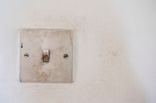 Close up of very dirty square light switch on stained white wall.の写真素材 [FYI02265820]