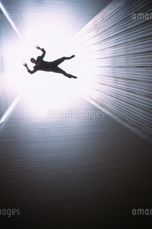 A conceptual silhouette of a businessman appearing to be falling down a long shaft lit by a bright lの写真素材 [FYI02265824]