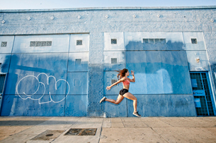Female athlete running along sidewalk past blue building covered in graffiti.の写真素材 [FYI02265825]
