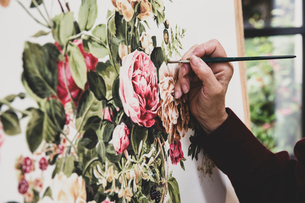 Close up of artist working on painting of pink tea roses, leaves, berries and other flowers.の写真素材 [FYI02265832]