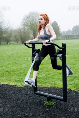 Young woman with long red hair wearing sports kit, using outdoor exercise machine.の写真素材 [FYI02265839]