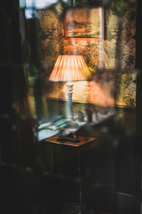 View through curtain of blue vintage table lamp with cream pleated lampshade.の写真素材 [FYI02265844]