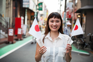 Smiling Japanese woman with long brown hair wearing white short-sleeved blouse standing in a street,の写真素材 [FYI02265851]
