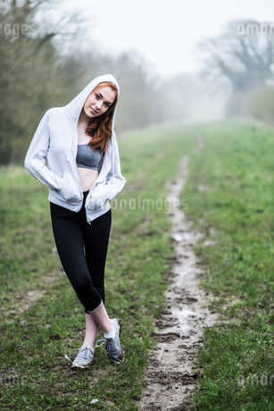Smiling young woman with long red hair wearing sports kit, exercising outdoors, looking at camera.の写真素材 [FYI02265854]