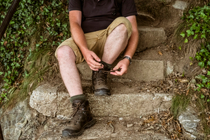 A man sitting tying up his walking boots laces on a stone step.の写真素材 [FYI02265873]