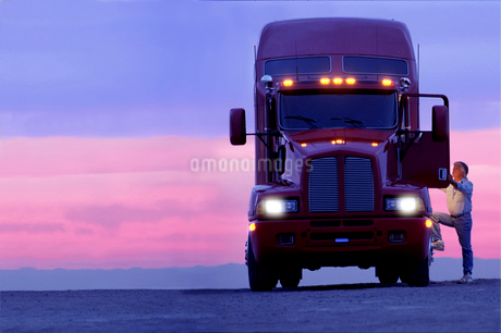 A silhouette of a truck driver getting into the cab of his commercial Class 8 truck tractor at sunriの写真素材 [FYI02265888]