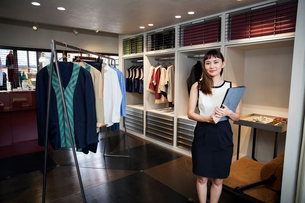 Smiling Japanese saleswoman standing in clothing store, holding file, smiling at camera.の写真素材 [FYI02265899]