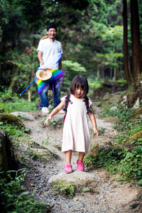 Japanese girl wearing pale pink sun dress and carrying backpack standing in a forest, man in the bacの写真素材 [FYI02265904]