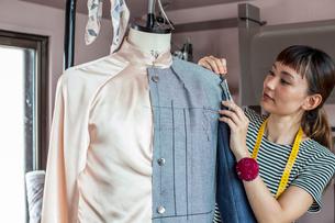 Japanese female fashion designer working on a garment on a dressmaker's model in a studio.の写真素材 [FYI02265907]