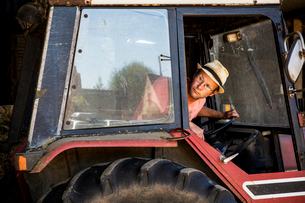 Farmer wearing straw hat and glasses driving red tractor.の写真素材 [FYI02265916]