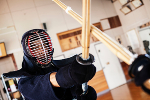 Two Japanese Kendo fighters wearing Kendo masks practicing with wood sword in gym.の写真素材 [FYI02265918]