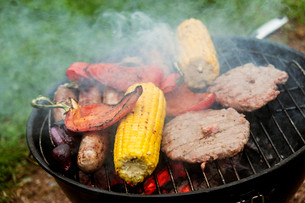 Food on a barbeque, vegetable kebabs and home made burgers, sweetcorn and peppers cooking.の写真素材 [FYI02265924]