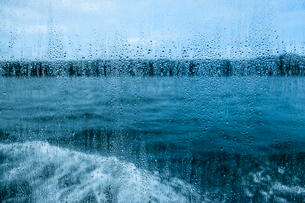 View through a rain spattered window over water and a boat's wake on an overcast day.の写真素材 [FYI02265925]