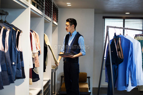 Japanese salesman with moustache wearing glasses standing in clothing store, looking at clothes on aの写真素材 [FYI02265937]