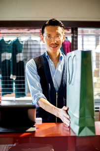 Japanese salesman with moustache wearing glasses standing at counter in clothing store, holding greeの写真素材 [FYI02265947]