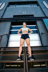 Low angle view of female athlete standing on steps in front of industrial building.の写真素材 [FYI02265948]