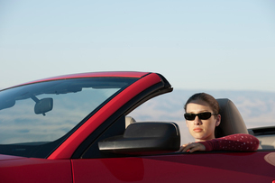 A young Caucasian woman in a convertible sports car.の写真素材 [FYI02265950]