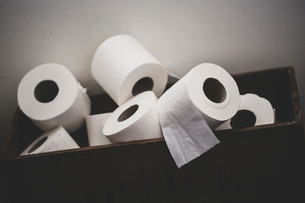 Close up of a pile of toilet paper rolls in a brown wooden crate.の写真素材 [FYI02265953]
