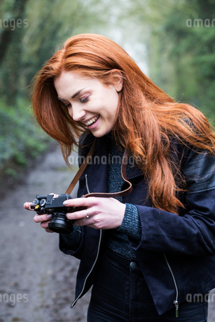 Smiling young woman with long red hair walking along forest path, taking pictures with vintage camerの写真素材 [FYI02265966]
