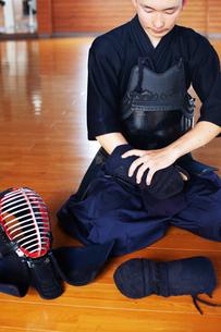 Male Japanese Kendo fighter kneeling on wooden floor, putting on Kote, hand protectors.の写真素材 [FYI02265972]
