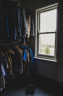 Interior view of walk-in wardrobe with sash window and clothing on clothes rails.の写真素材 [FYI02265976]