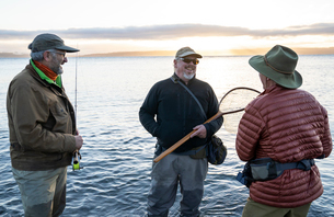 Two fly fisherman talk with their guide about new techniques while fly fishing for searun coastal cuの写真素材 [FYI02265979]
