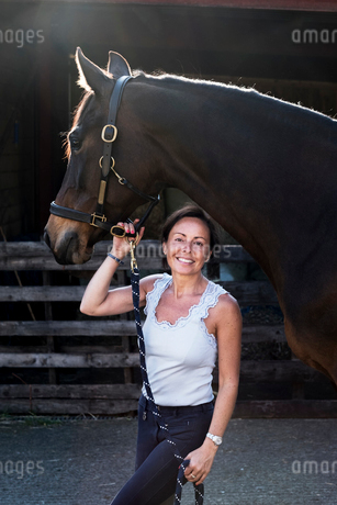 Smiling woman standing outdoor at stable, holding brown horse by rein.の写真素材 [FYI02265983]